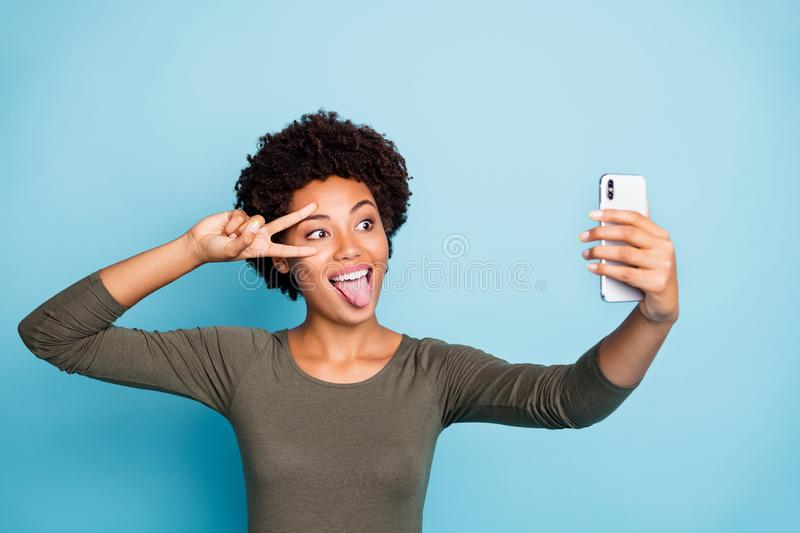 Photo of cute cheerful nice attractive black skinned woman fooling before camera showing v-sign sticking out wearing royalty free stock photo