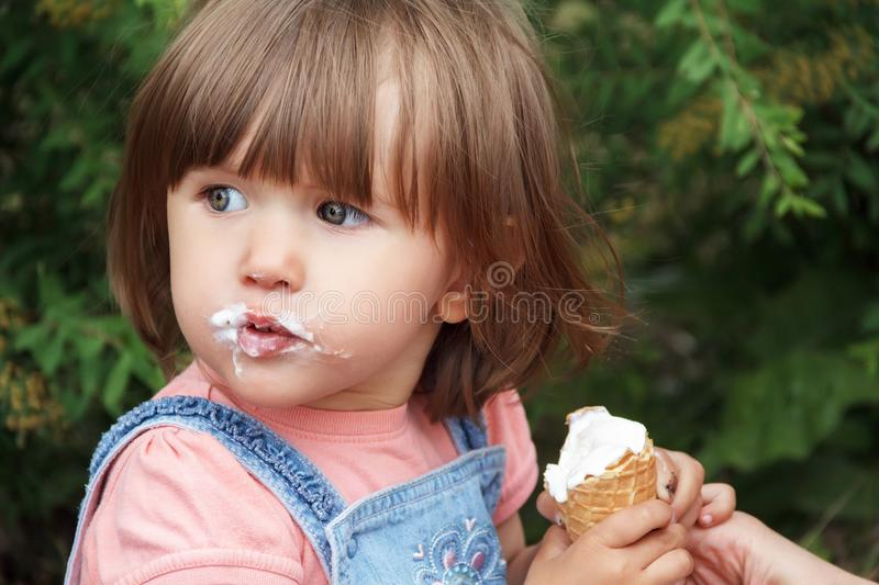 Cute girl are eating icecream. Photo of cute girl eating icecream in summer royalty free stock photos