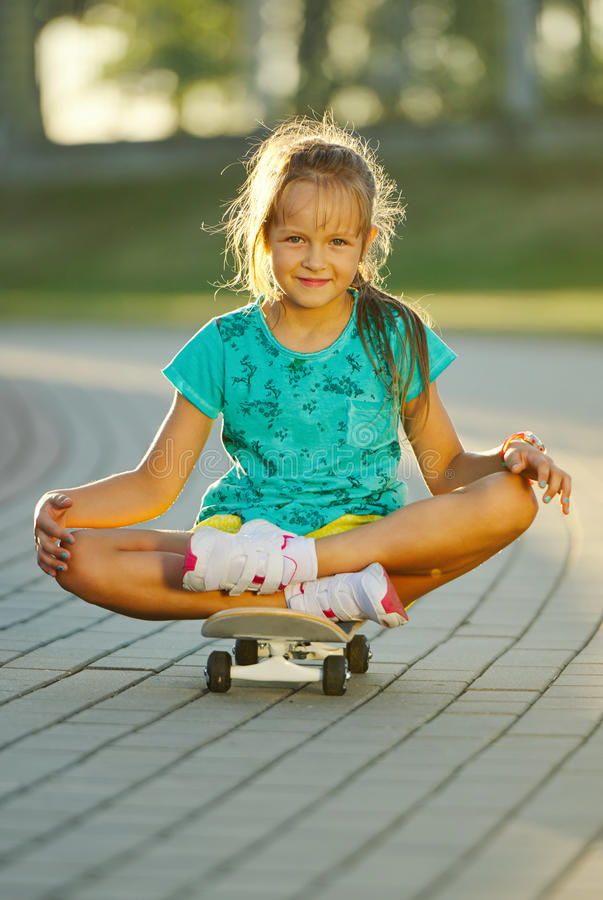 Photo of cute little girl with skateboard royalty free stock image