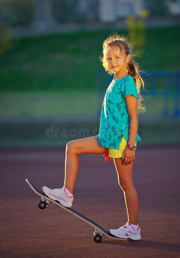 Photo of cute little girl with skateboard outdoors royalty free stock photos