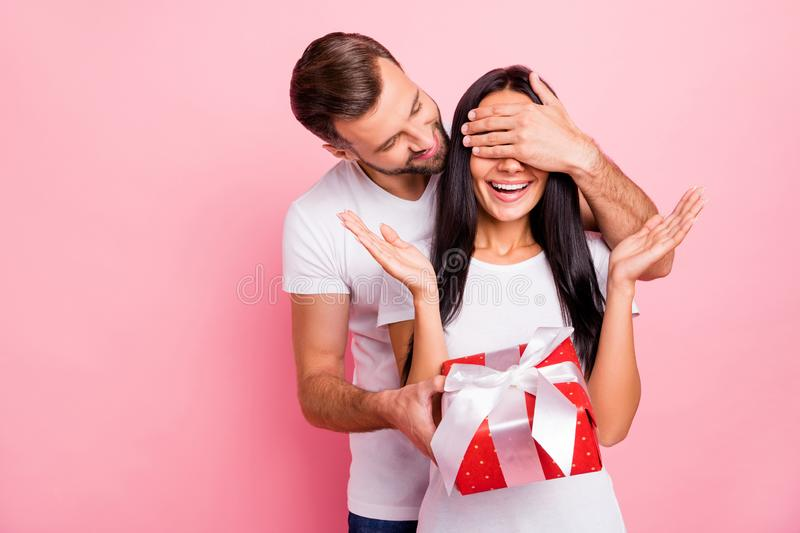 Photo of cute nice couple of fallen in love liking to gift each other red package with bow while isolated with pink. Photo of cute nice couple of fallen in love royalty free stock photos