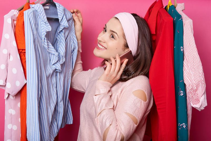 Photo of cute young girl standing in store near clothes rack and holding mobile phone, speaking with somebody, dressed rose shirt stock photo