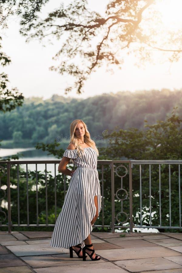 Photo d'élève de terminale d'extérieur caucasien blond de fille dans la robe de barboteuse images stock