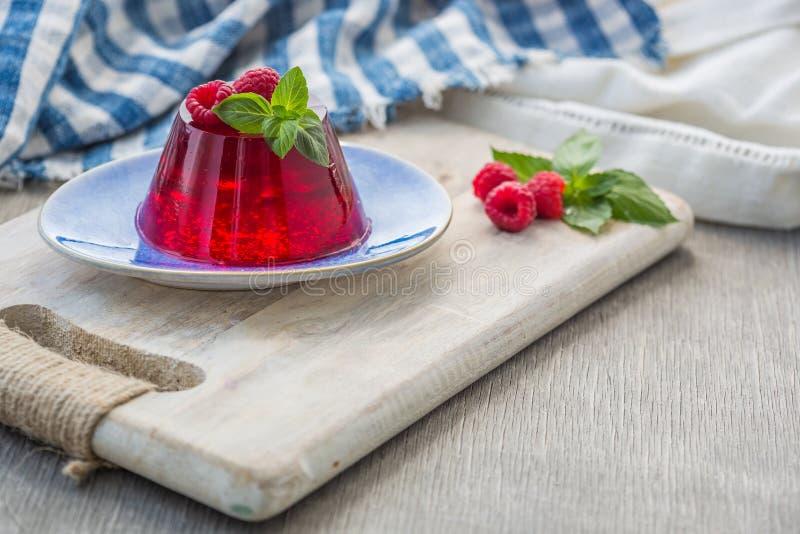 Photo d'été Jelly Dessert avec la framboise Garni avec un brin de basilic frais sur le fond clair images stock