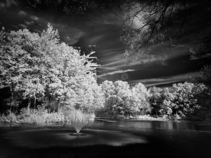 Photo d'art infrarouge d'un étang avec fontaines d'eau photo libre de droits