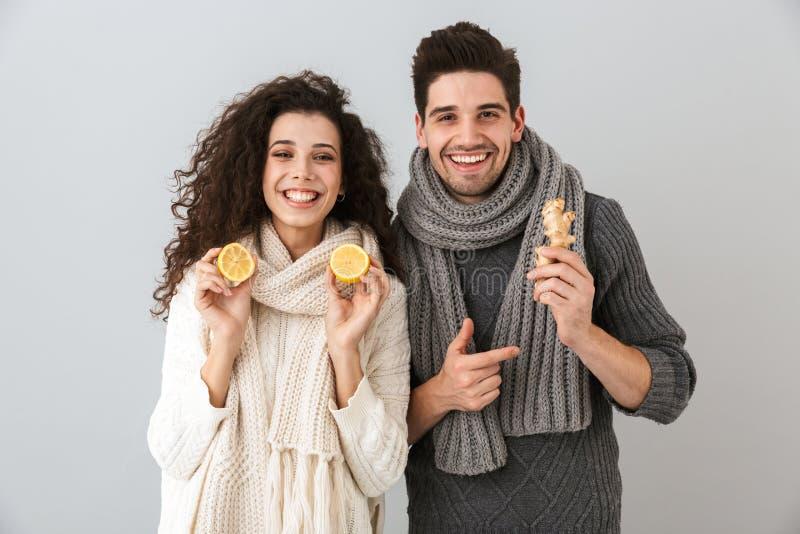 Photo d'homme en bonne santé de couples et d'écharpes de port de femme tenant les citrons et le gingembre, d'isolement au-dessus  image libre de droits