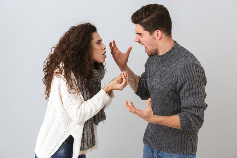 Photo d'homme fâché et de femme criant à l'un l'autre se tenant face à face, d'isolement au-dessus du fond gris image stock