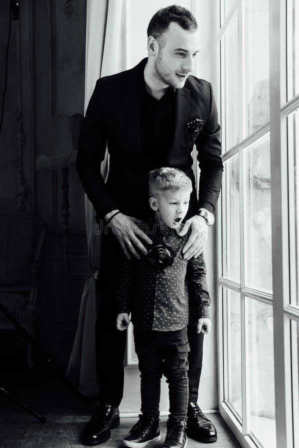Photo d'homme heureux et son de fils s'asseyant par la fenêtre photos stock