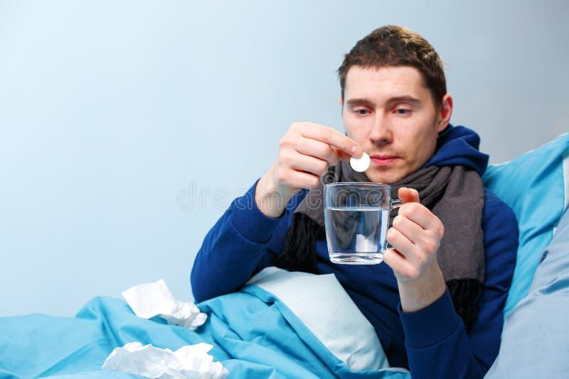 Photo d'homme malade dans l'écharpe avec le comprimé et la tasse se situant dans le lit photos stock