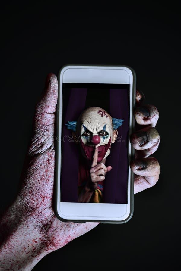 Photo d'un clown mauvais dans un smartphone photographie stock libre de droits