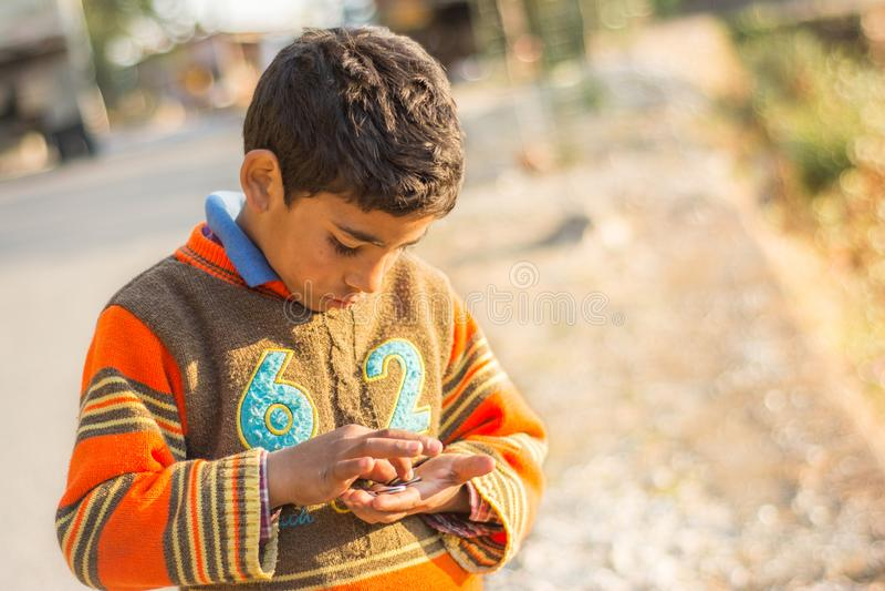 Photo d'un garçon indien regardant vers le bas et comptant des pièces de monnaie dans des ses mains pendant l'après-midi chez Mus images libres de droits