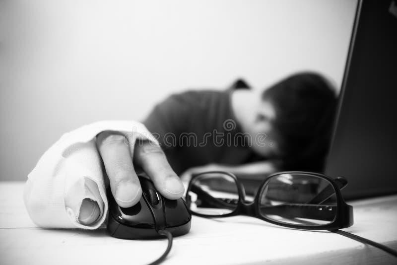Photo d'un homme avec des blessures essayant de travailler sur son ordinateur photographie stock
