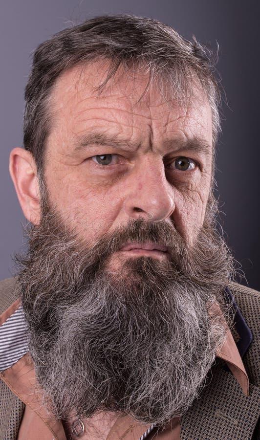 Photo d'un vieil homme grincheux fâché regardant très contrarié Homme masculin avec la longue barbe sur son visage Fermez-vous ve photo libre de droits