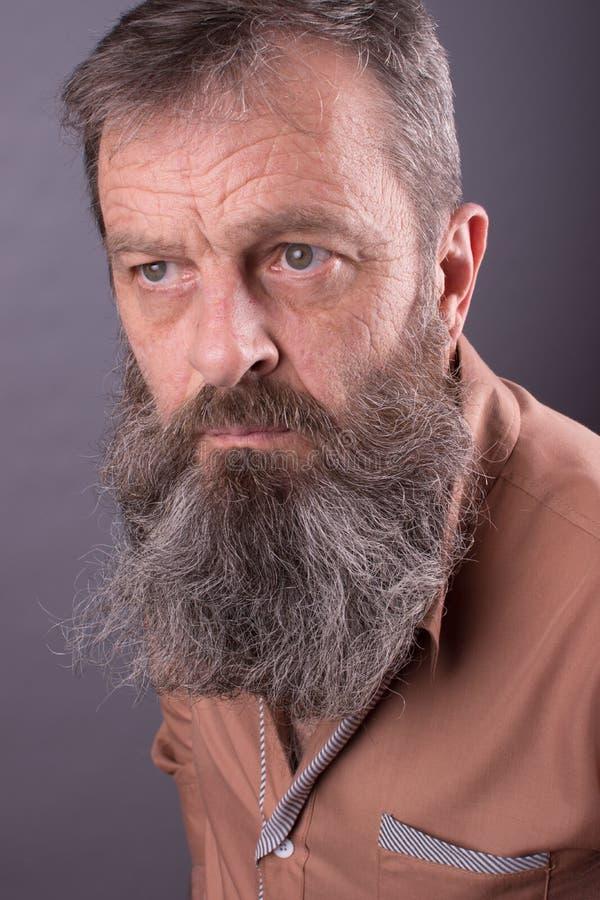 Photo d'un vieil homme grincheux fâché regardant très contrarié Homme masculin avec la longue barbe sur son visage Fermez-vous ve image stock