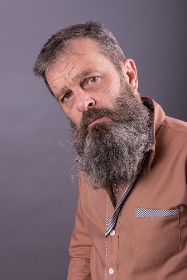 Photo d'un vieil homme grincheux fâché regardant très contrarié Homme masculin avec la longue barbe sur son visage Fermez-vous ve photo stock