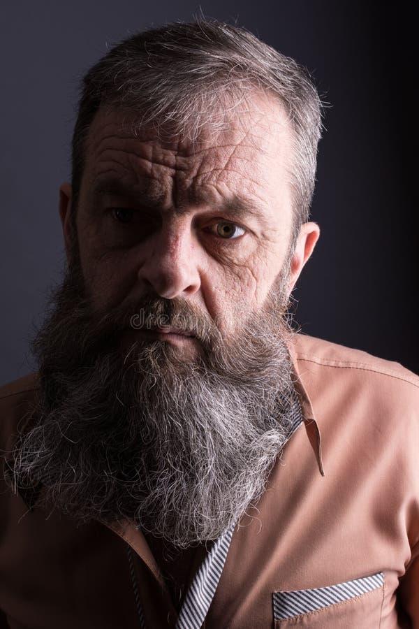 Photo d'un vieil homme grincheux fâché regardant très contrarié Homme masculin avec la longue barbe sur son visage Fermez-vous ve images stock