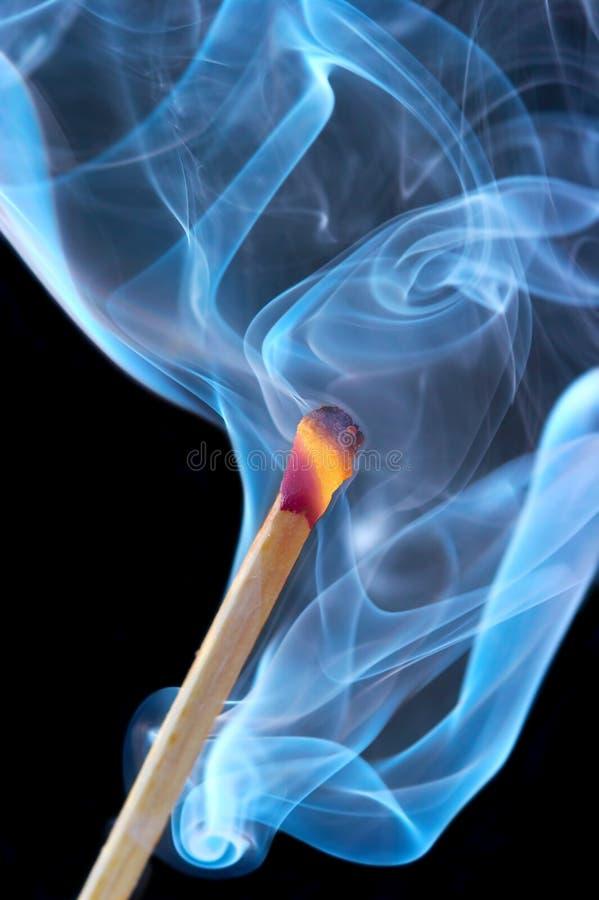 Photo d'une allumette brûlante dans une fumée sur un fond noir image stock