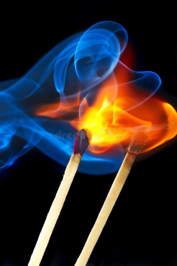 Photo d'une allumette brûlante dans une fumée sur un fond noir photographie stock