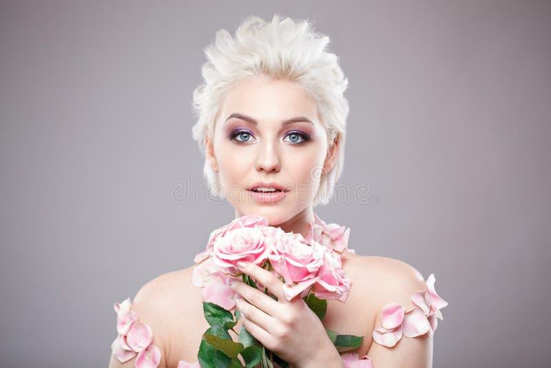 Photo d'une belle femme blonde avec la fleur Visage sensuel attrayant de plan rapproché de la femme blanche avec les cheveux bouc photographie stock libre de droits