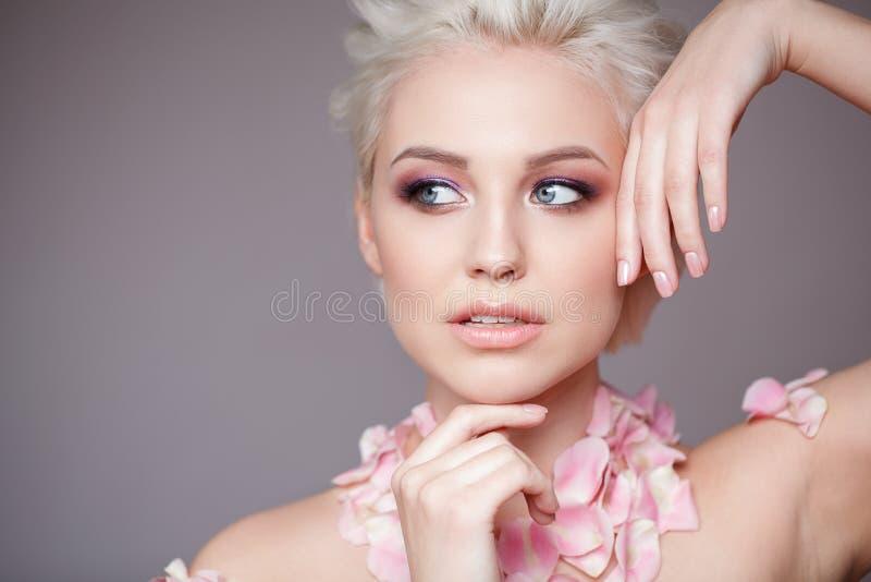Photo d'une belle femme blonde avec la fleur Visage sensuel attrayant de plan rapproché de la femme blanche avec les cheveux bouc image stock