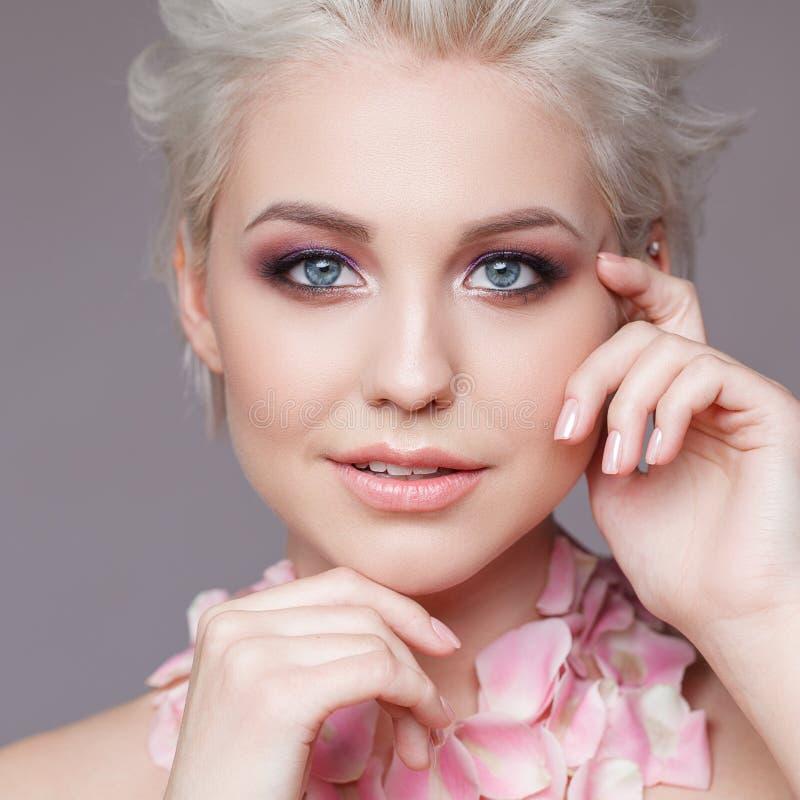 Photo d'une belle femme blonde avec la fleur Visage sensuel attrayant de plan rapproché de la femme blanche avec les cheveux bouc photographie stock