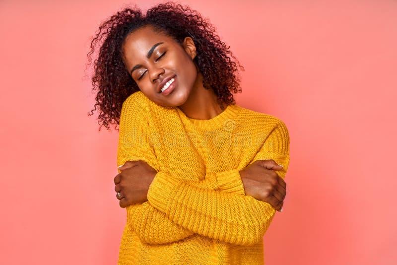 Photo d'une belle femme noire souriante s'embrasse, a une haute estime de soi, ferme les yeux de la joie, aime sa nouvelle photographie stock