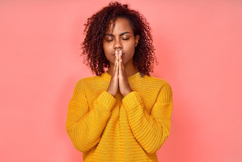 Photo d'une belle jeune femme noire se tient la main dans un geste de prière, ferme les yeux, jouit d'une atmosphère paisible photos libres de droits