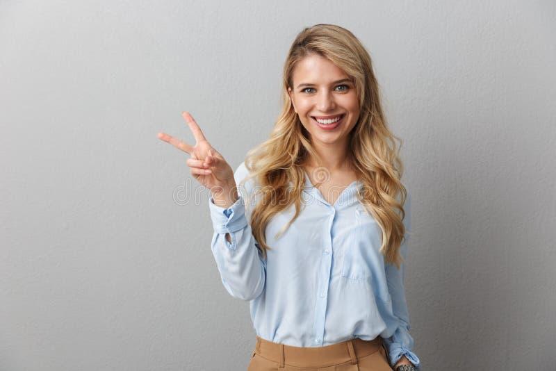 Photo d'une femme d'affaires aux longs cheveux bouclés souriant et montrant un signe de paix isolé sur fond gris image stock