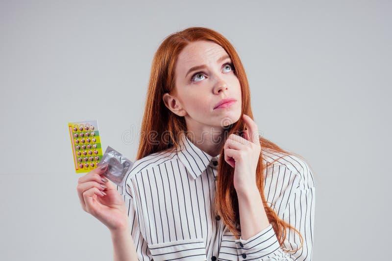 Photo d'une jeune rousse perdue dans une femme d'affaires imaginaire en chemise rayée avec un paquet de pilules pensant blanc photos stock