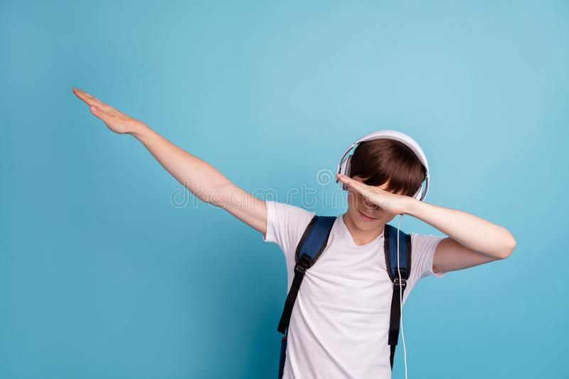 Photo of dancing rejoicing enjoying cheerful boy hiding his eyes behind his hand while isolated with blue background stock photography