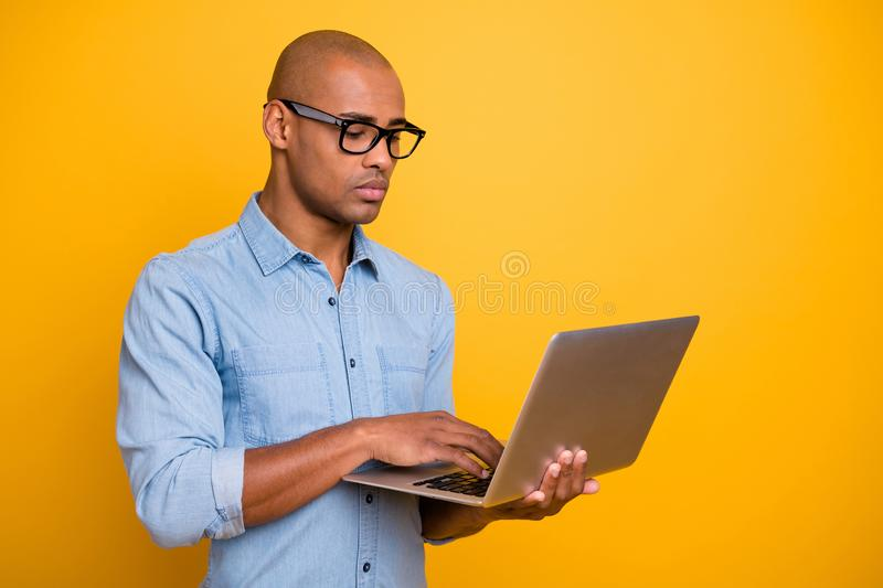Photo of dark skin business man not smiling browsing notebook wear specs jeans denim shirt isolated bright yellow royalty free stock image