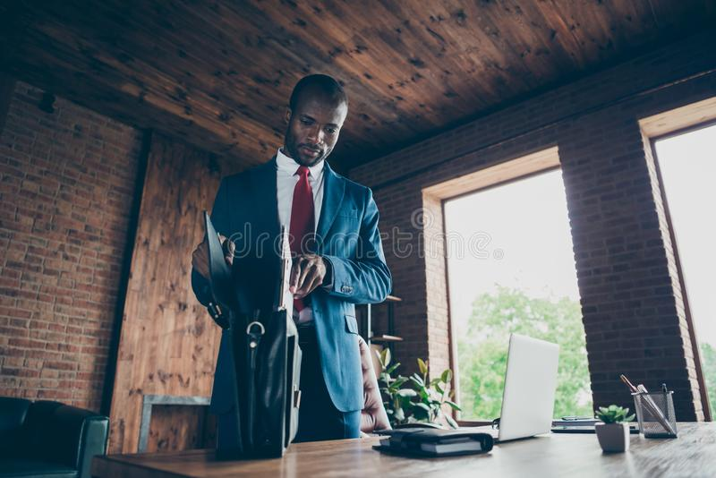 Photo of dark skin guy packing own documents papers into bag wear elegant costume. Photo of dark skin guy packing, own documents papers into bag wear elegant stock image