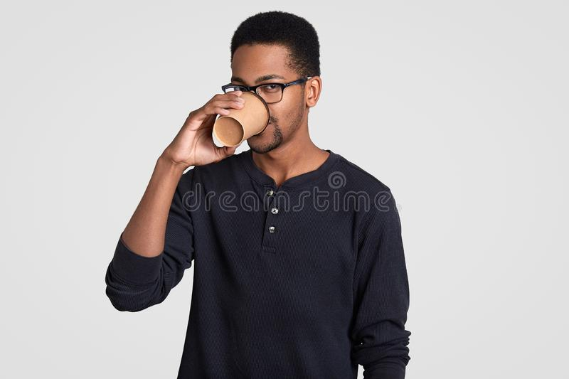 Photo of dark skinned guy with curly hair, drinks coffee from disposable cup, dressed in casual black sweater, spectacles, stands royalty free stock photos