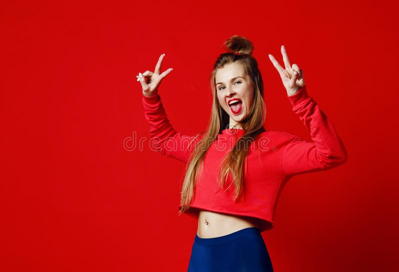 Photo de beau, souriant, fille positive montrant le symbole de paix, regardant la caméra, posant sur le fond coloré photos stock