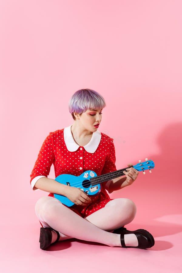 Photo de belle fille dollish avec les cheveux violet-clair courts portant la robe rouge jouant l'ukulélé bleue au-dessus du rose images libres de droits