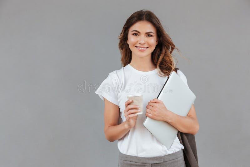 Photo de belle jeune femme souriant et se tenant contre le gris photo libre de droits