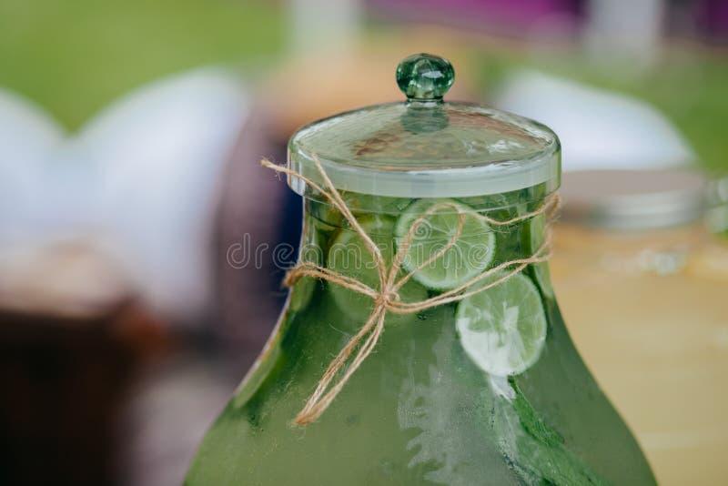 Photo de boisson fraîche de chaux dans le conteneur en verre Citronnade froide Projectile horizontal Compote avec des vitamines d photos libres de droits