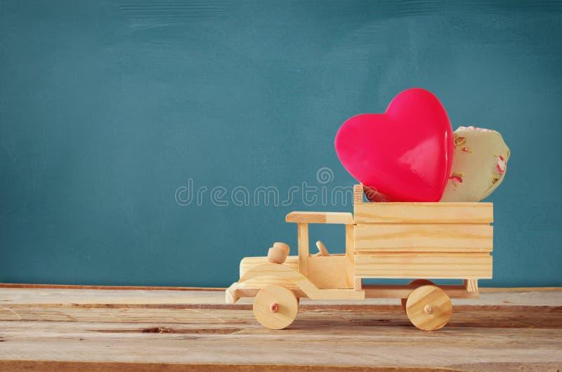 Photo de camion en bois de jouet avec des coeurs devant le tableau Concept de célébration de Saint-Valentin photo stock