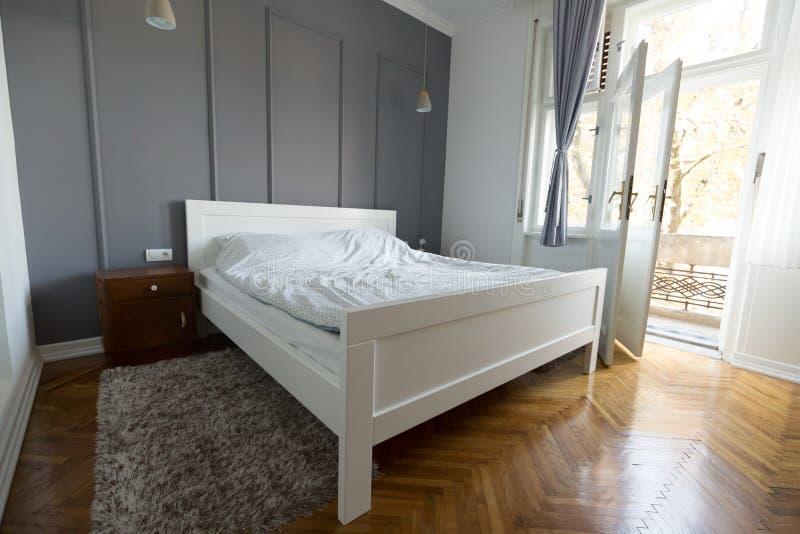 Photo de chambre à coucher dans les couleurs claires douces et le lit confortable image libre de droits