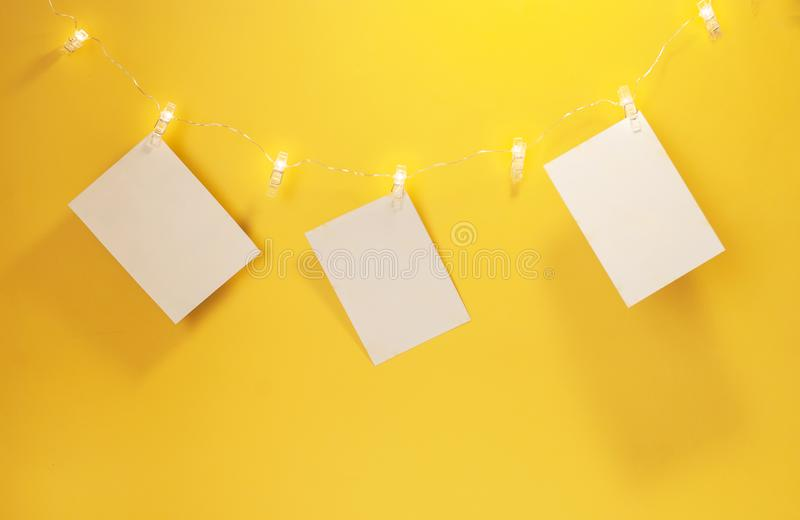 Photo de Clothespin guirlande lumineuse avec une place pour la photographie sur fond jaune Fête photographie stock libre de droits