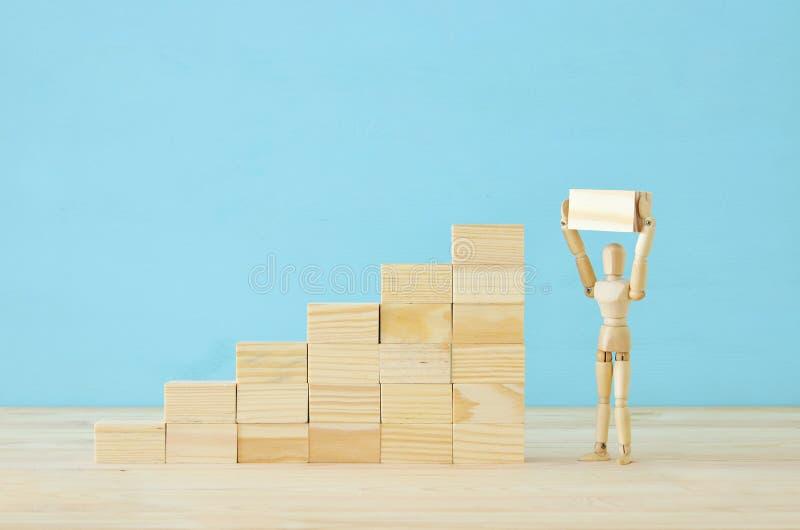 photo de concept du franchissement d'obstacles, du simulacre en bois regardant une barrière et pensant à la solution photographie stock