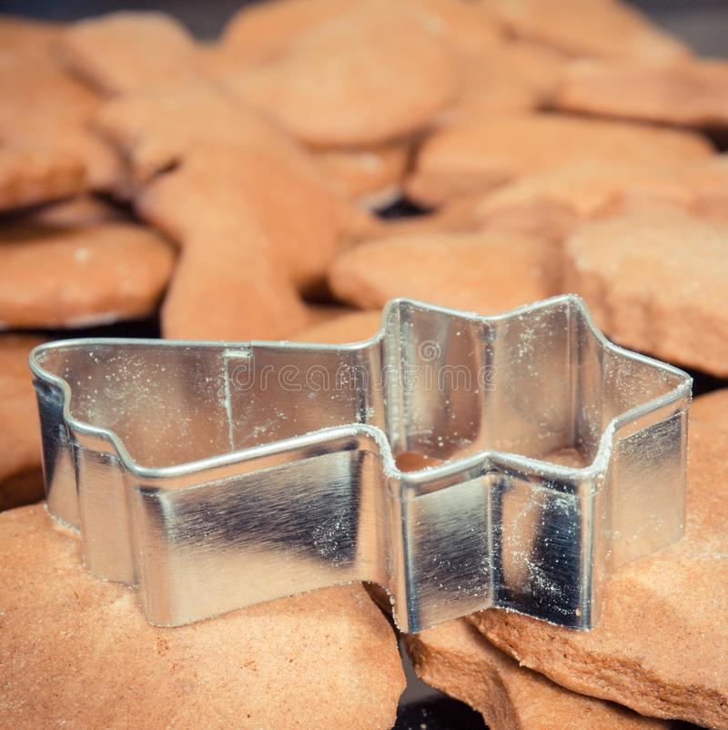 Photo de cru, coupeurs de biscuit dans la forme de l'étoile et pain d'épice ou biscuits cuits au four frais pour Noël photos libres de droits