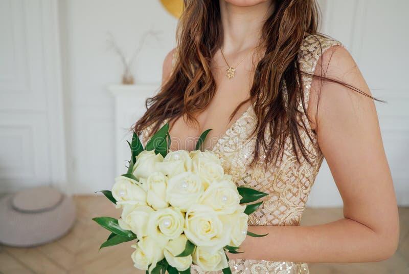 Photo de culture de jeune mariée dans la belle robe d'or avec le bouquet de mariage des roses blanches dans des mains, fin  photo stock