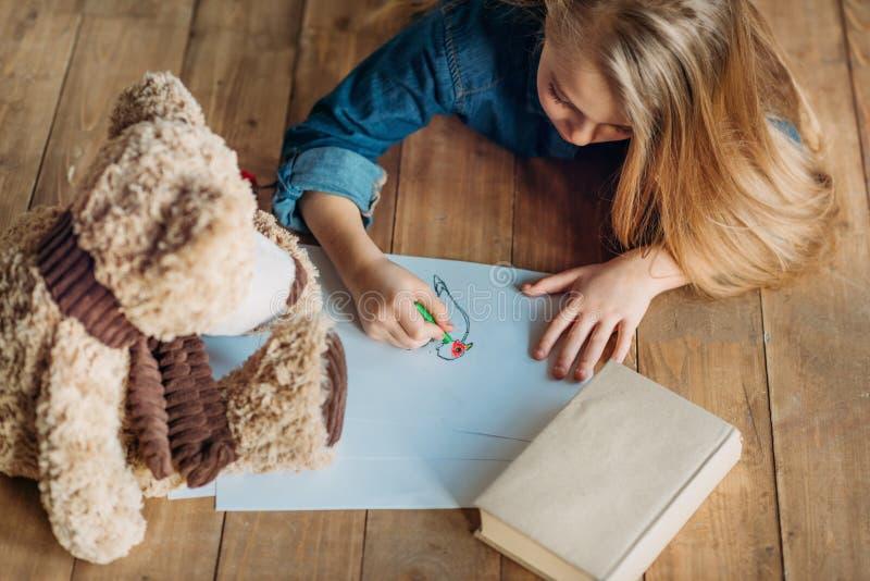 Photo de dessin de fille sur le plancher à la maison, enfants dessinant le concept photo libre de droits