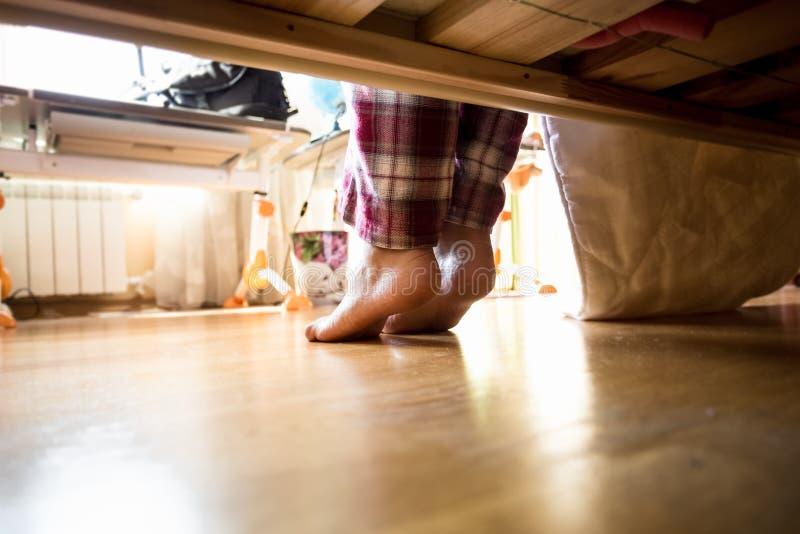 Photo de dessous le lit sur la femme aux pieds nus dans des pyjamas image libre de droits