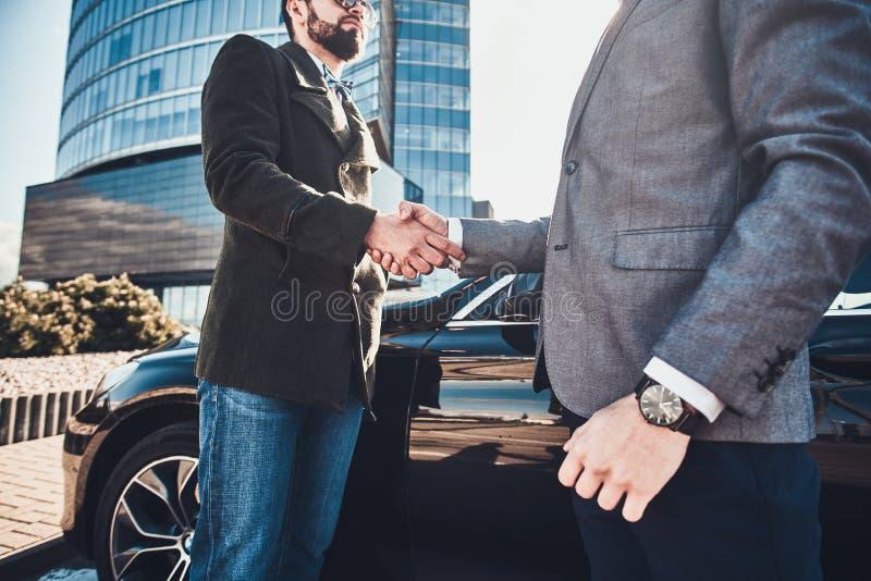 Photo de deux hommes élégants futés, qui ont une affaire au sujet de voiture images libres de droits