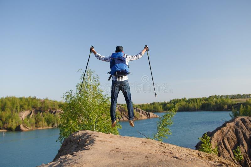 Photo de dos d'homme de touristes avec des cannes sautant sur la colline de montagne près du lac photographie stock