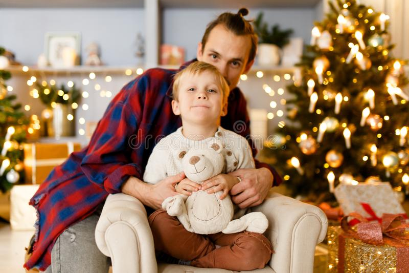 Photo de fête du père embrassant son fils s'asseyant sur la chaise photographie stock libre de droits