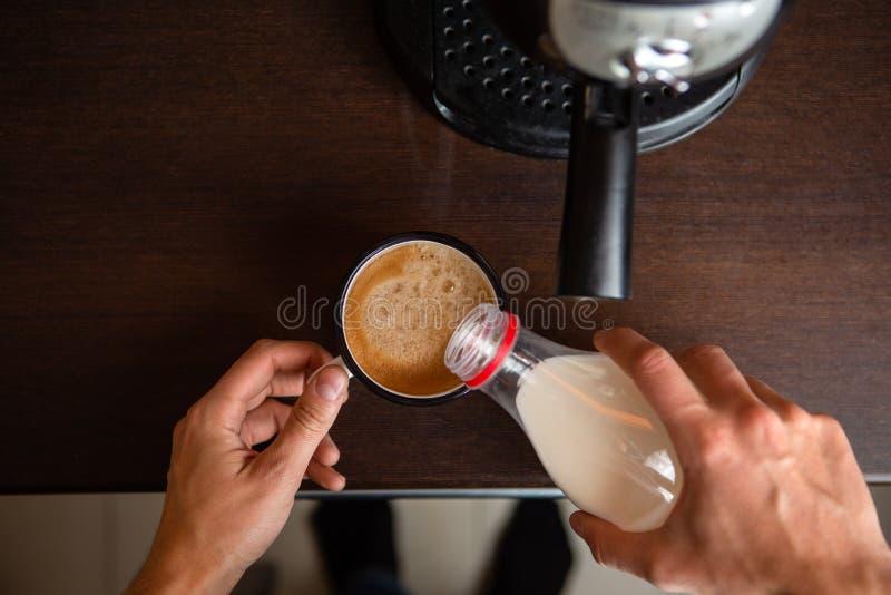 Photo de fabricant de café, les mains de l'homme versant le lait dans la tasse de café photo stock