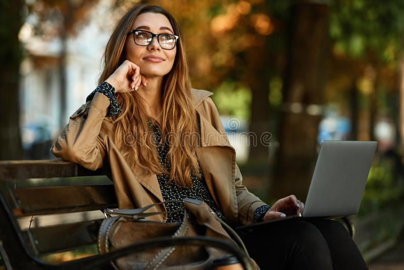 Photo de femme affable travaillant sur l'ordinateur portable tout en se reposant sur le banc dans l'allée ensoleillée photo stock
